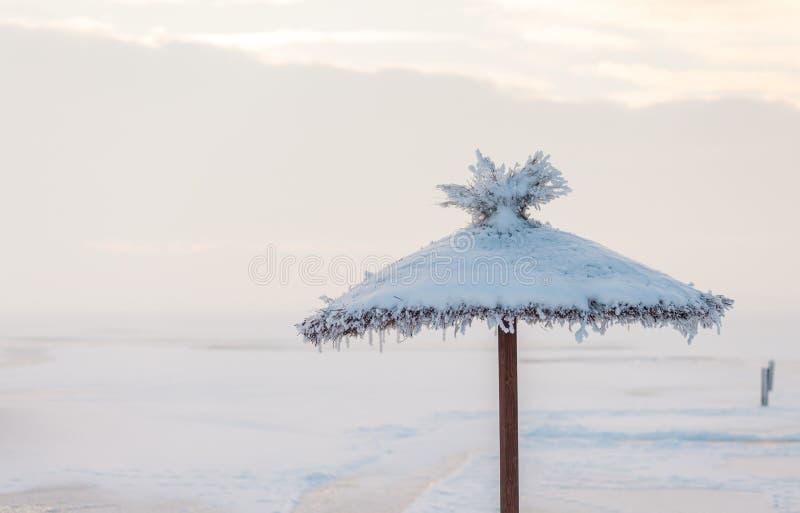 Zonnescherm met sneeuw op het strand in de winter wordt behandeld die stock foto's
