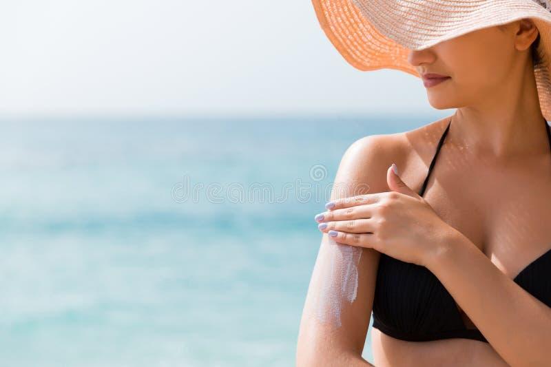Zonnescherm sunblock Vrouw in een hoed die zonneroom op schouder zetten in openlucht onder zonneschijn op mooie de zomerdag stock fotografie