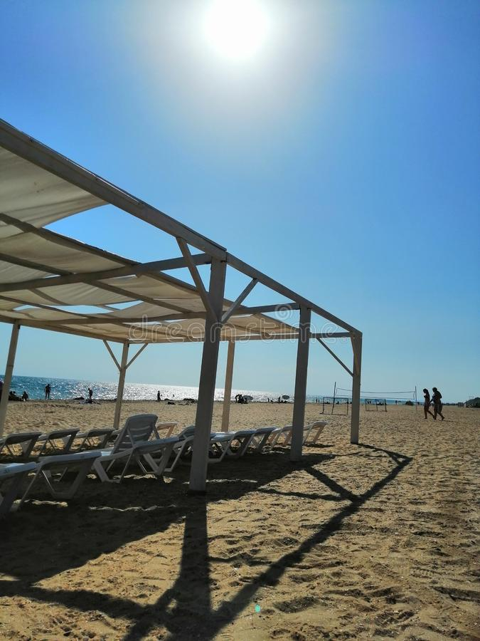 Zonnescherm, zonbedden op een zandig strand stock fotografie