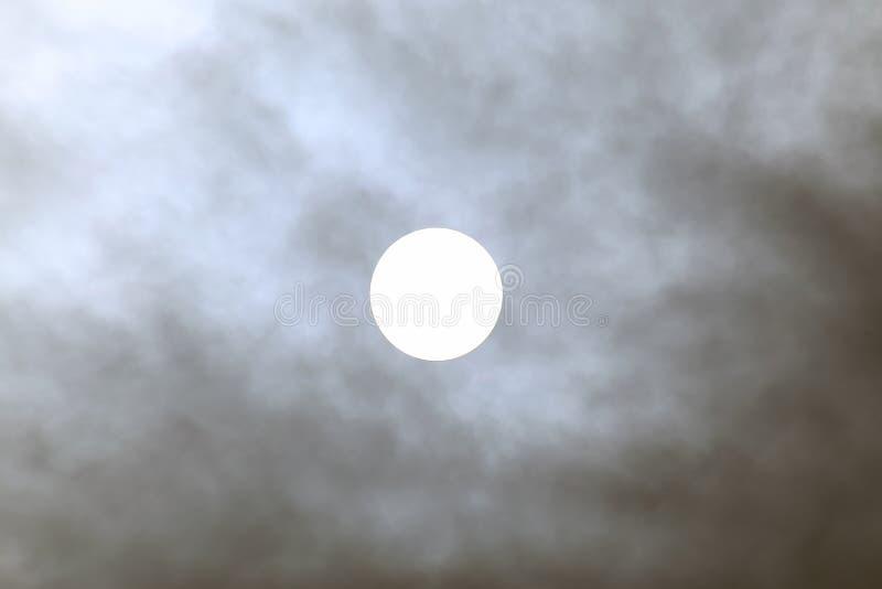 Zonneschijf bij middag door de wolken stock afbeeldingen