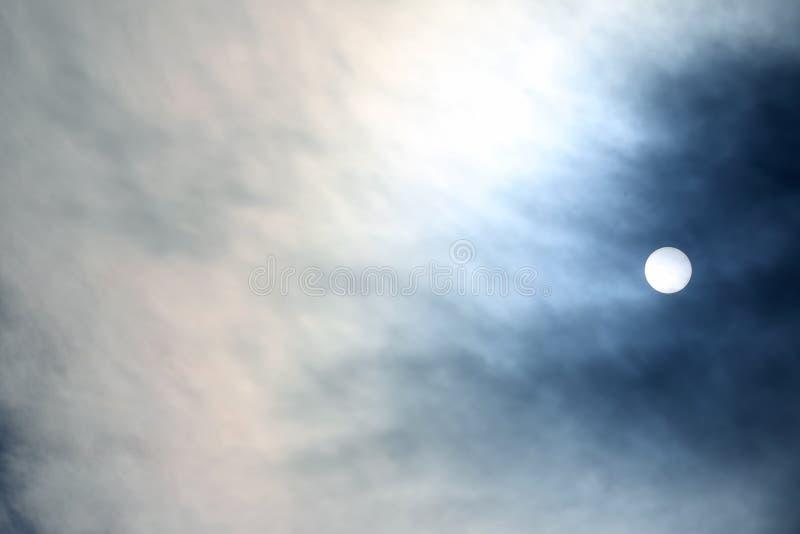 Zonneschijf bij middag door de wolken stock fotografie