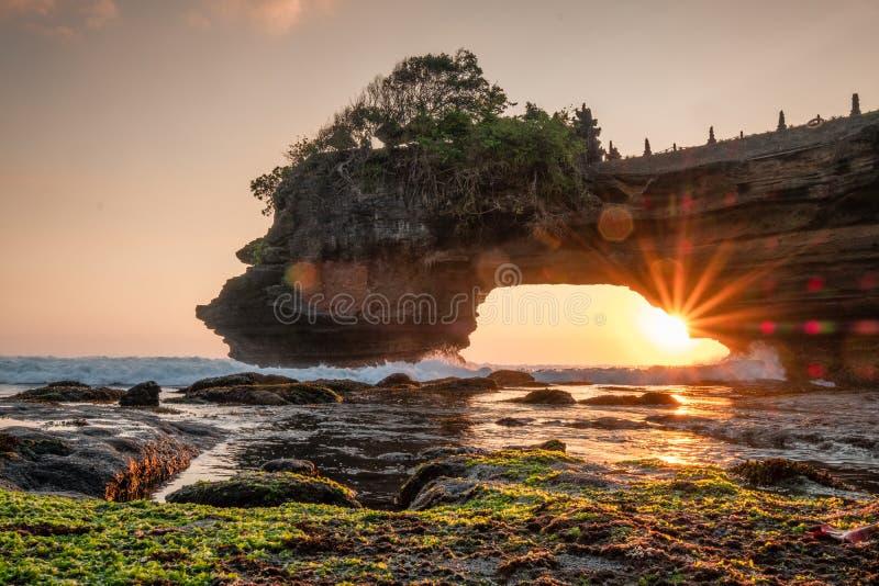 Zonneschijn door van rotsachtige klip op kust bij zonsondergang royalty-vrije stock fotografie