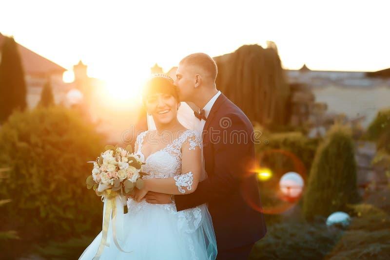 Zonneschijnportret van gelukkige bruid en bruidegom openlucht in aardplaats bij zonsondergang De warme dag van het zomerhuwelijk royalty-vrije stock foto