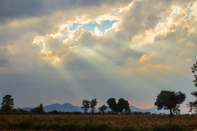 Zonnestraal die door de wolk in de vallei glanzen Avondzonsondergang met zonstralen door de wolken royalty-vrije stock foto's