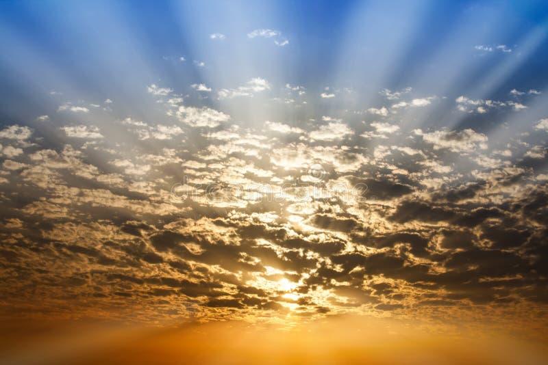 Zonnestraal door wolken blauwe en oranje hemel royalty-vrije stock afbeelding
