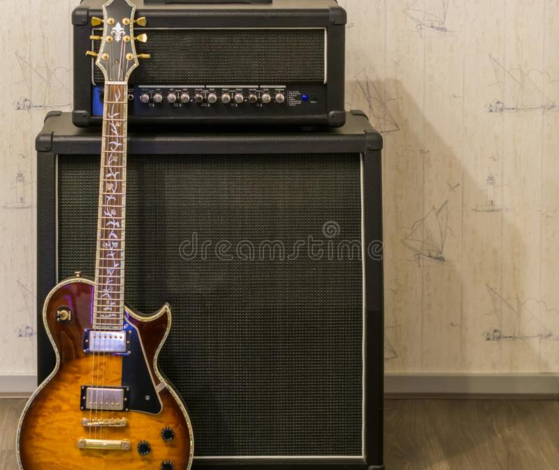 Zonnestraal elektrische gitaar die zich voor een versterker en een correcte effect doos, professioneel muziekmateriaal bevinden stock foto