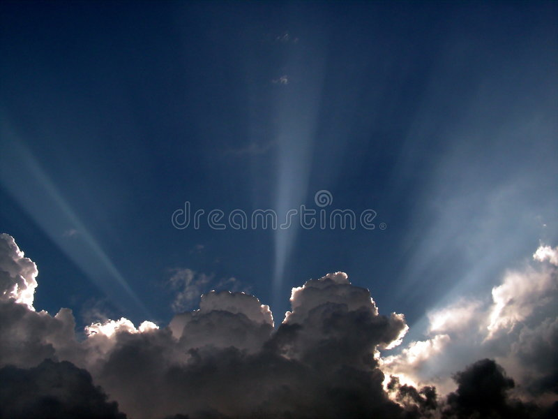 Zonnestraal over wolken stock afbeelding