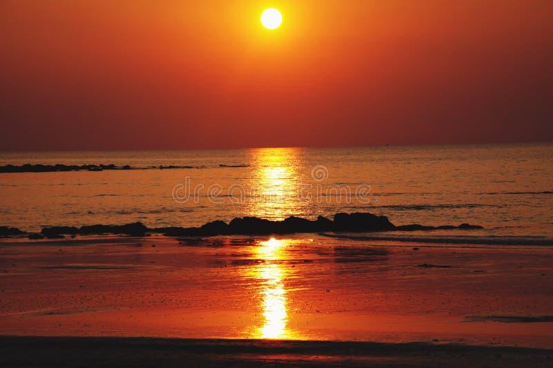 Zonnestraal tijdens de lange gele straal van het zonsondergangafgietsel van licht over de oceaan en op ondiep water tijdens eb Ko stock foto's