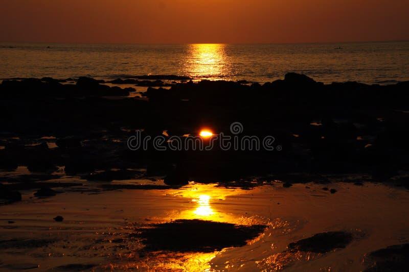 Zonnestraal tijdens de lange gele straal van het zonsondergangafgietsel van licht over de oceaan stock foto's
