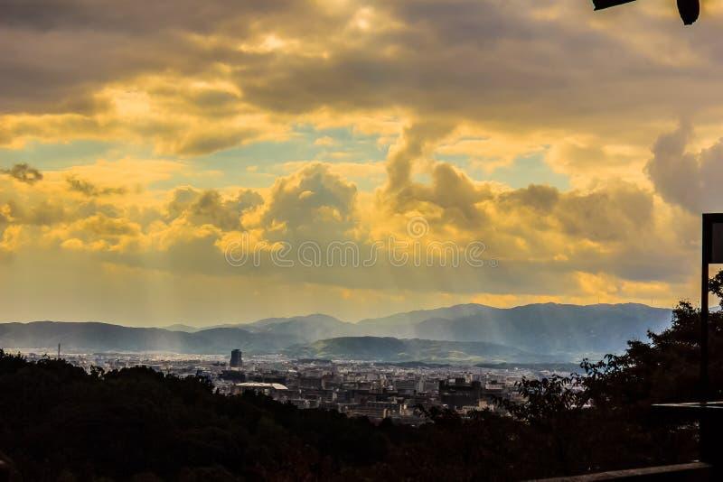 Zonnestralen die door de wolken over de stad van Kyoto, Japa glanzen stock afbeeldingen