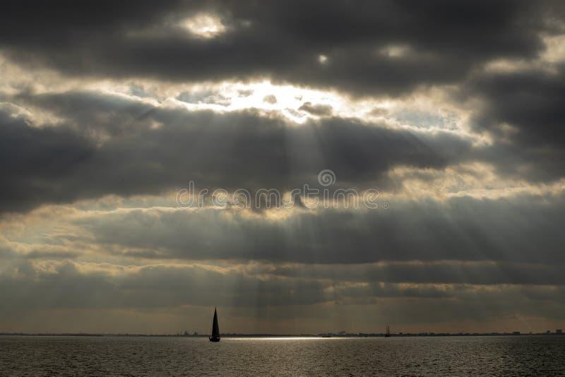 Zonnestralen die door wolkendekking breken, een zeilboot die op een meer dichtbij Amsterdam varen stock fotografie