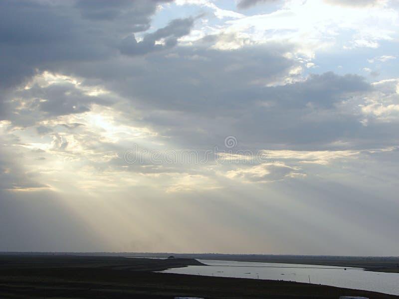 Zonnestralen door Wolken die over een Rivier uitspreiden stock afbeelding