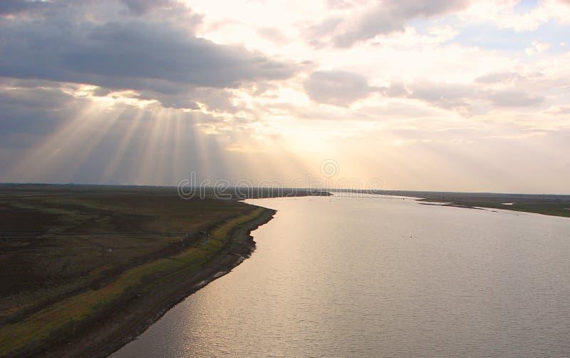 Zonnestralen door Wolken die over een Rivier uitspreiden stock foto
