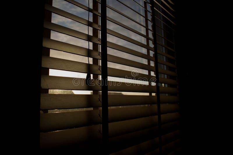 Zonnestralen glanzende trog sommige zonneblinden stock fotografie