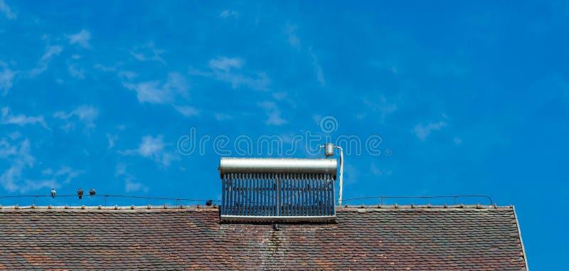 Zonnewaterverwarmer op oud dak, vogels, vogelsuitwerpselen op de waterboiler royalty-vrije stock fotografie