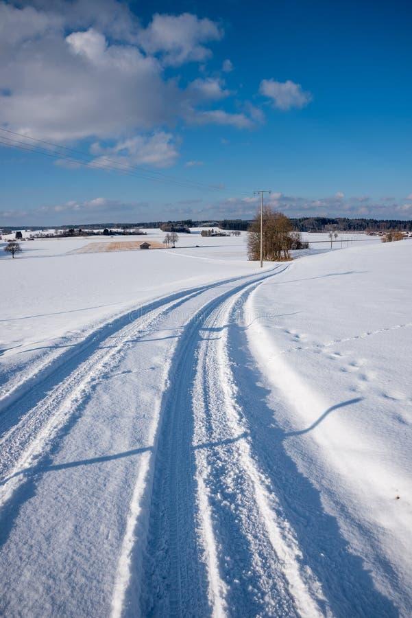 Zonnig de winterlandschap met sneeuwlandweg in landelijk landschap royalty-vrije stock fotografie