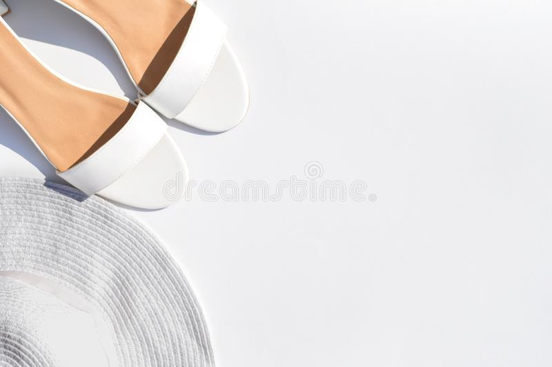 In Zonnig de zomerconcept met witte sandals, witte strandhoed op witte achtergrond met hard licht stock foto