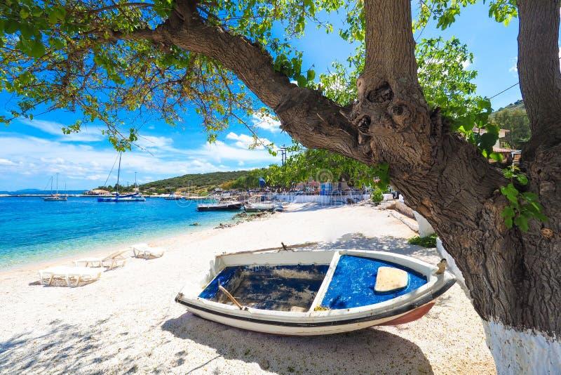 Zonnig de zomerstrand in Griekenland met zonbedden en kleine boot royalty-vrije stock afbeeldingen