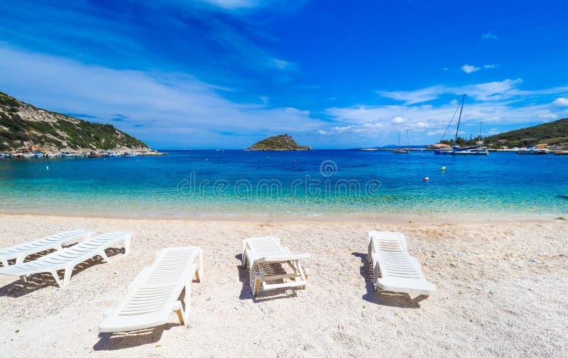 Zonnig de zomerstrand in Griekenland met zonbedden en kleine boot royalty-vrije stock fotografie