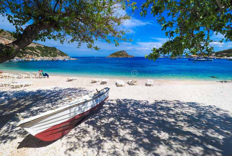 Zonnig de zomerstrand in Griekenland met zonbedden en kleine boot Agio's stock fotografie