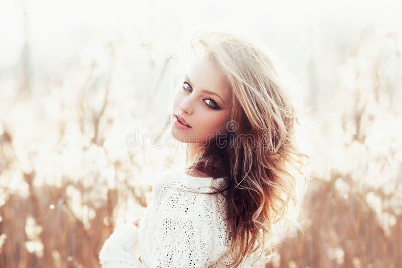 Zonnig portret van een mooi jong blondemeisje op een gebied in witte trui, het concept gezondheid en schoonheid stock fotografie