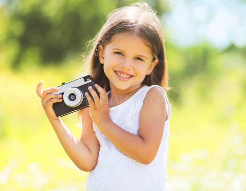 Zonnig portret van leuk glimlachend meisjekind met oude camera royalty-vrije stock foto