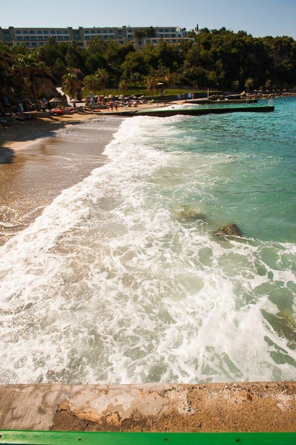 Zonnig strand met toeristen de golven wassen het strand royalty-vrije stock afbeelding