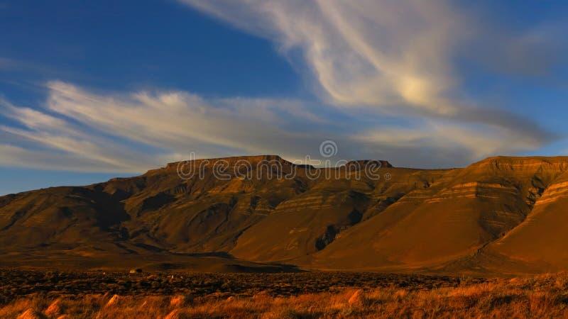 Zonnige bergen Wolken door de Wind over de Top worden geblazen die Blauwe hemel royalty-vrije stock afbeeldingen