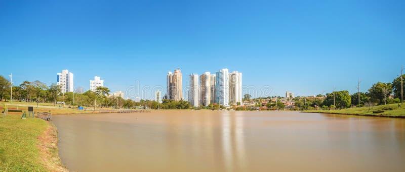 Zonnige dag bij een meer van een park met aard en weinig gebouwen op B royalty-vrije stock foto