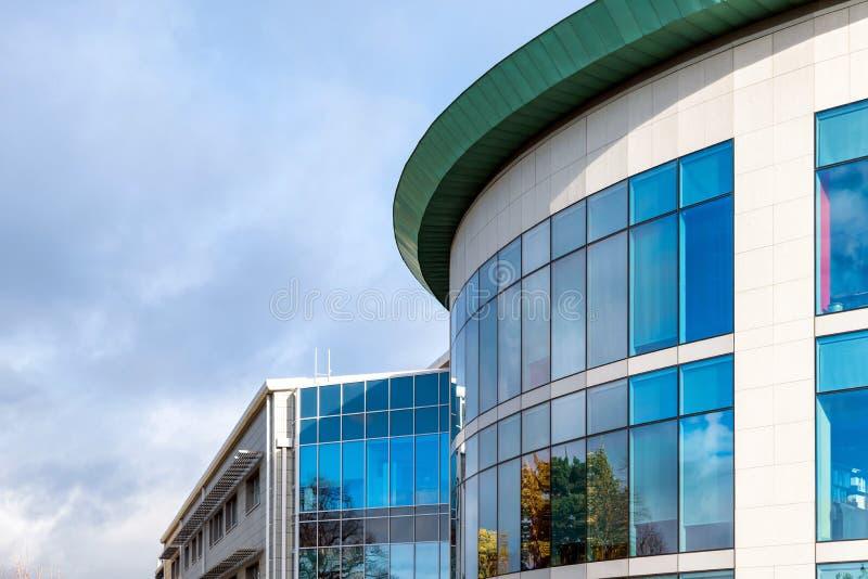 Zonnige dagmening van vensters van de moderne bedrijfs collectieve bureaubouw in Engeland het UK van Northampton stock afbeelding