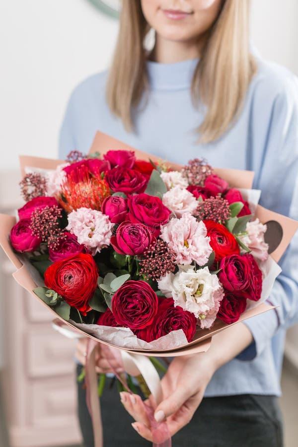 Zonnige de lenteochtend Jonge gelukkige vrouw die een mooi luxeboeket van gemengde bloemen houden het werk van de bloemist bij stock fotografie