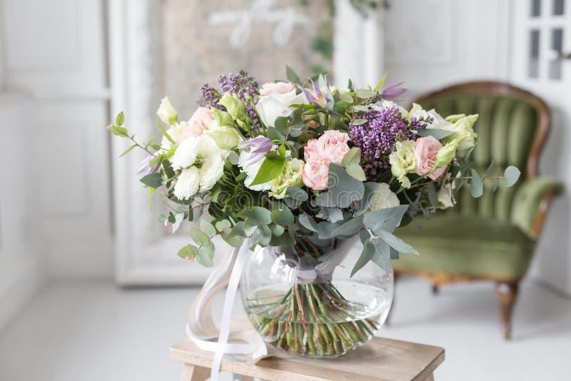 Zonnige de lenteochtend in woonkamer Mooi luxeboeket van gemengde bloemen in glasvaas het werk van royalty-vrije stock foto's