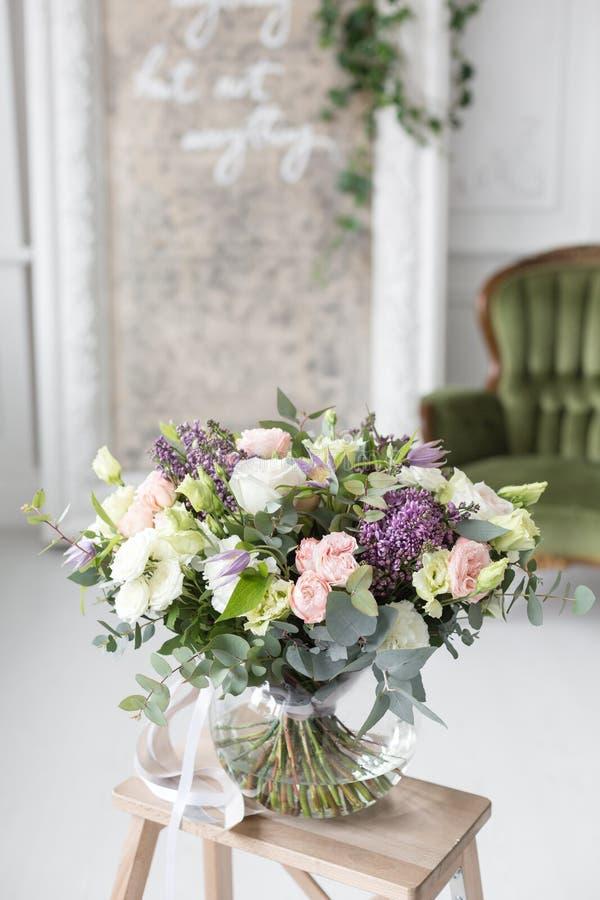 Zonnige de lenteochtend in woonkamer Mooi luxeboeket van gemengde bloemen in glasvaas het werk van royalty-vrije stock fotografie