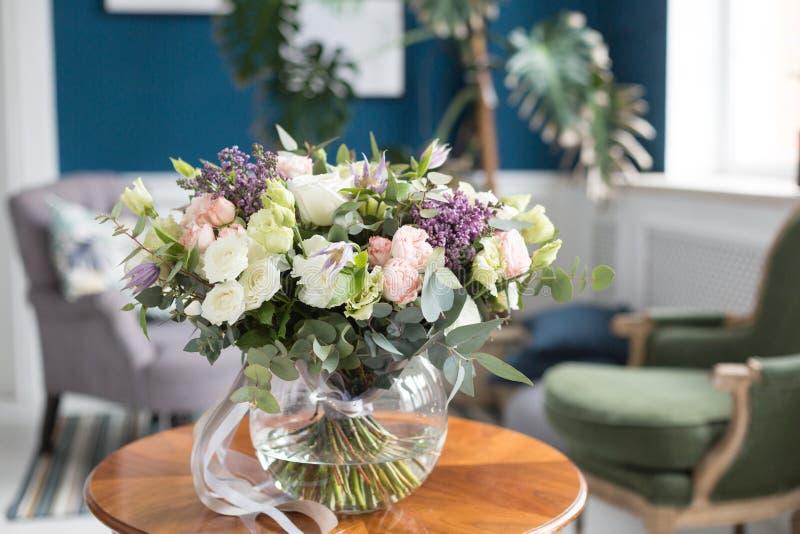Zonnige de lenteochtend in woonkamer Mooi luxeboeket van gemengde bloemen in glasvaas op houten lijst Het werk royalty-vrije stock fotografie
