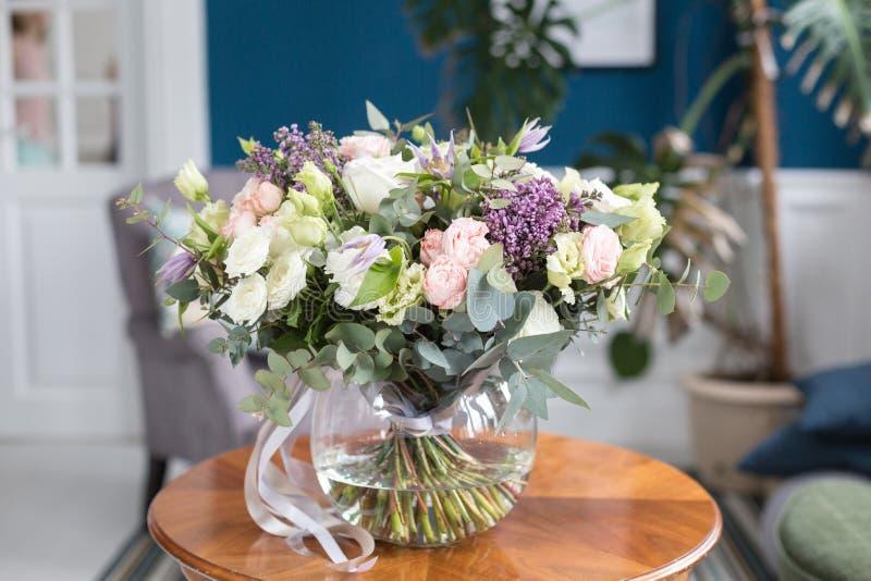 Zonnige de lenteochtend in woonkamer Mooi luxeboeket van gemengde bloemen in glasvaas op houten lijst Het werk stock foto