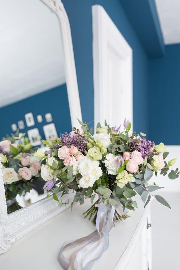 Zonnige de lenteochtend in woonkamer Mooi luxeboeket van gemengde bloemen in glasvaas op houten lijst Het werk stock afbeelding