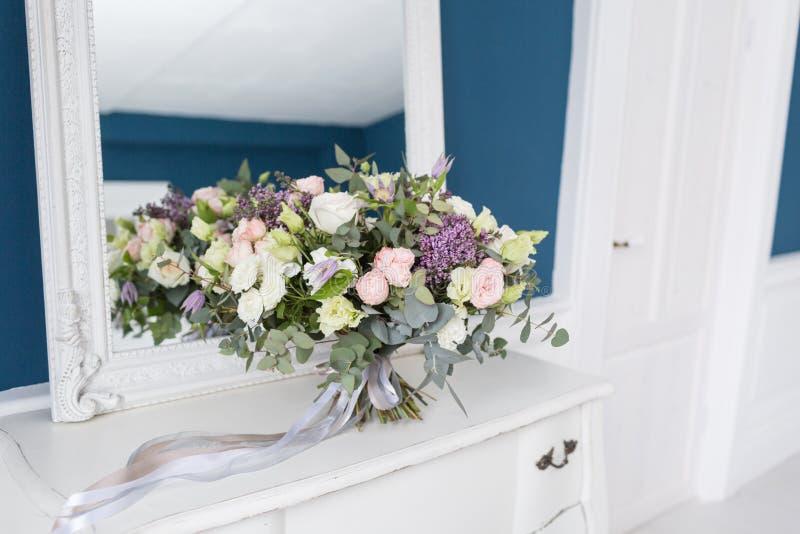 Zonnige de lenteochtend in woonkamer Mooi luxeboeket van gemengde bloemen in glasvaas op houten lijst Het werk stock afbeeldingen
