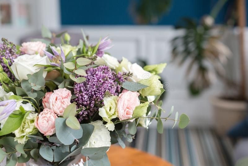 Zonnige de lenteochtend in woonkamer Mooi luxeboeket van gemengde bloemen in glasvaas op houten lijst Het werk stock fotografie