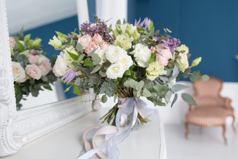 Zonnige de lenteochtend in woonkamer Mooi luxeboeket van gemengde bloemen in glasvaas op houten lijst Het werk royalty-vrije stock afbeeldingen