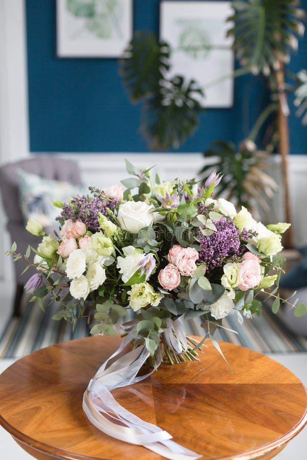 Zonnige de lenteochtend in woonkamer Mooi luxeboeket van gemengde bloemen op houten lijst het werk van stock foto's