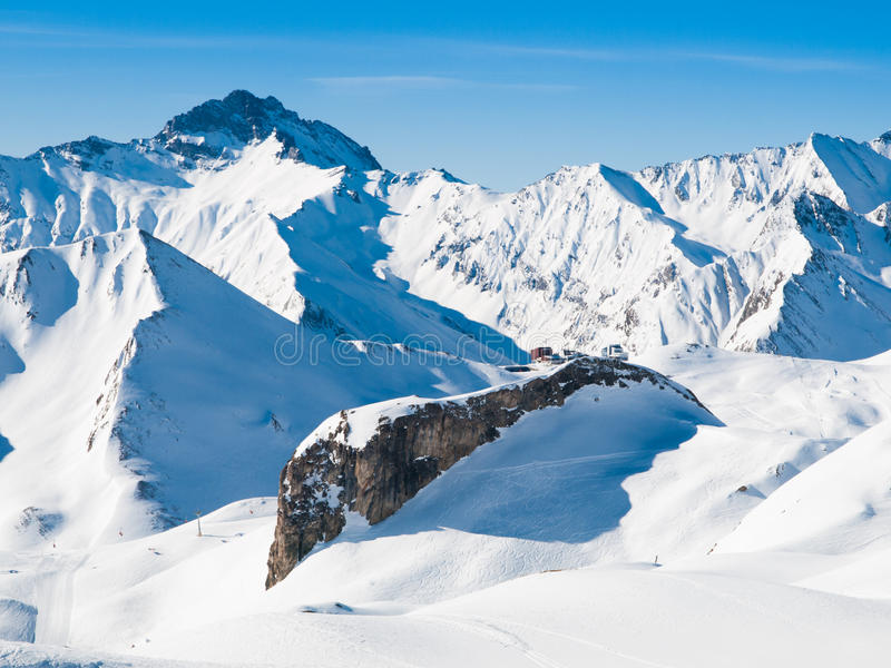 Zonnige de winterdag in alpiene skitoevlucht stock afbeeldingen