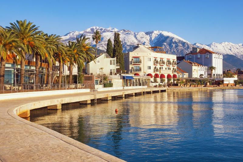 Zonnige de winterdag Montenegro, Baai van Kotor Dijk van Tivat-stad en sneeuwpieken van Lovcen-berg royalty-vrije stock foto's