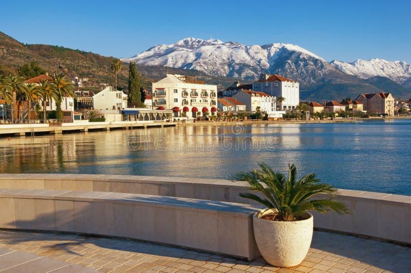 Zonnige de winterdag Montenegro, Baai van Kotor Weergevendijk van Tivat-stad en sneeuwpieken van Lovcen-berg stock afbeelding