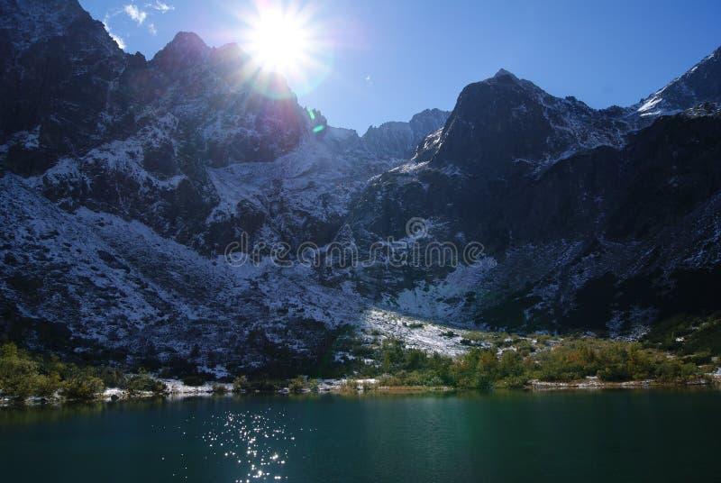 Zonnige en ijzige berg met meer stock fotografie