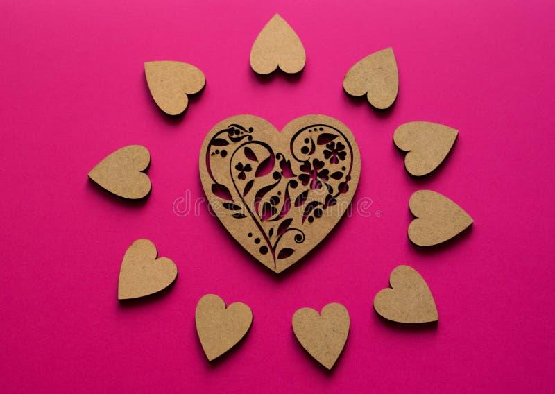 Zonnige hartensamenstelling van hoogste mening over roze achtergrond Pook-trekkend houten hart in het centrum stock afbeeldingen