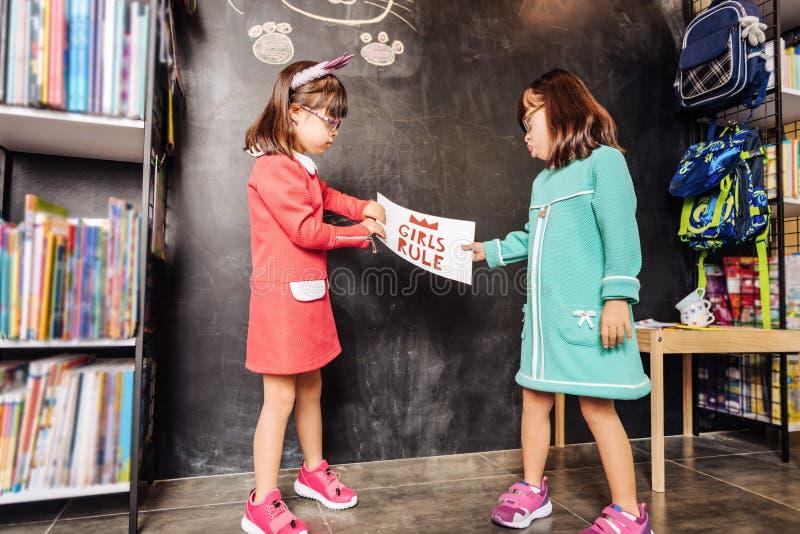Zonnige kinderen die heldere tennisschoenen dragen die zich dichtbij bord bevinden royalty-vrije stock fotografie