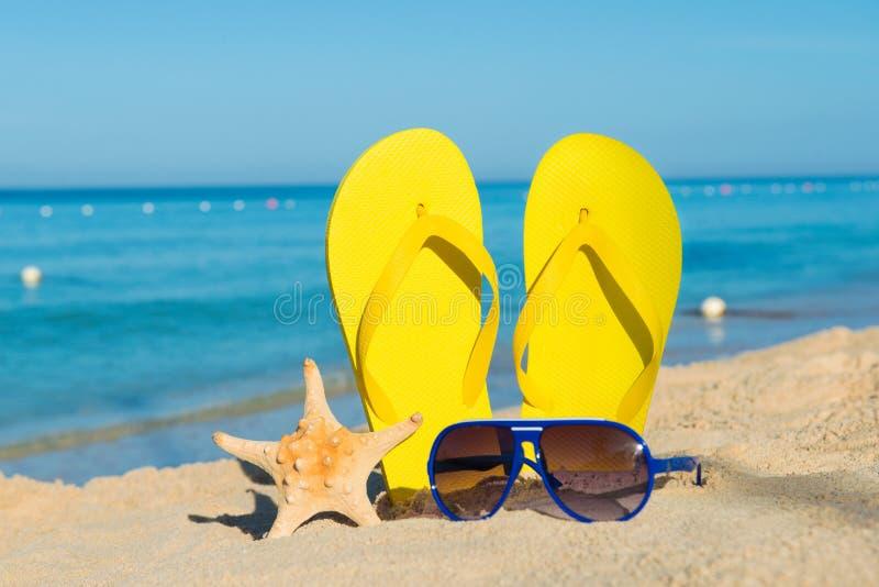 Zonnige positieve strandvakantie Gele sandals, zonnebril en zeester op een achtergrond van het overzees royalty-vrije stock foto's
