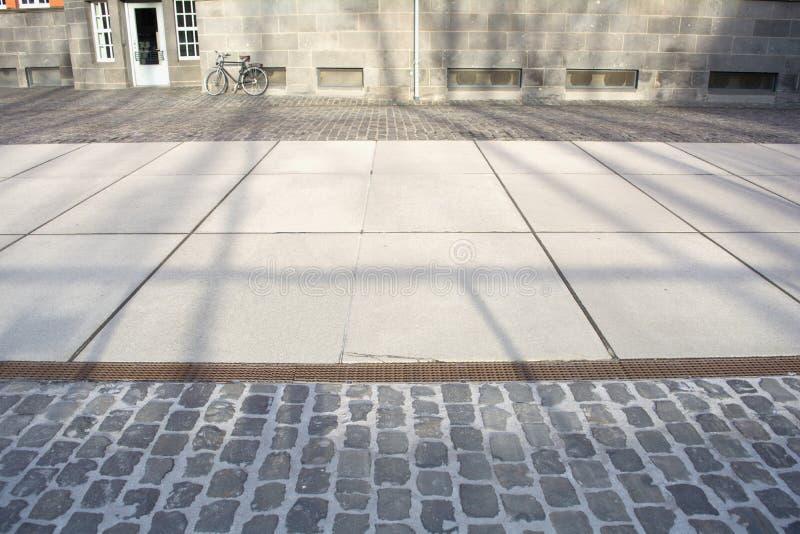 Zonnige straat met schaduwen en bycicle royalty-vrije stock afbeelding