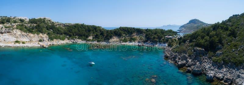 Zonnige strandlagune met rotsachtige kustlijn, Griekenland De toeristen onder paraplukou ontspannen dichtbij duidelijk blauw smar royalty-vrije stock fotografie