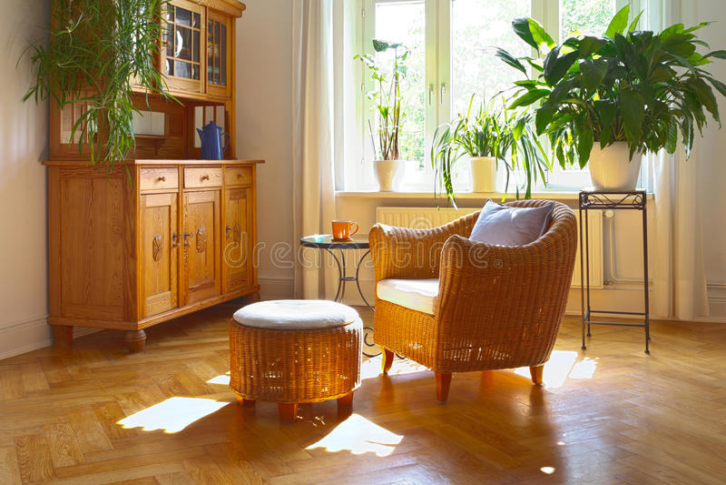 Zonnige woonkamer rieten stoel stock foto's